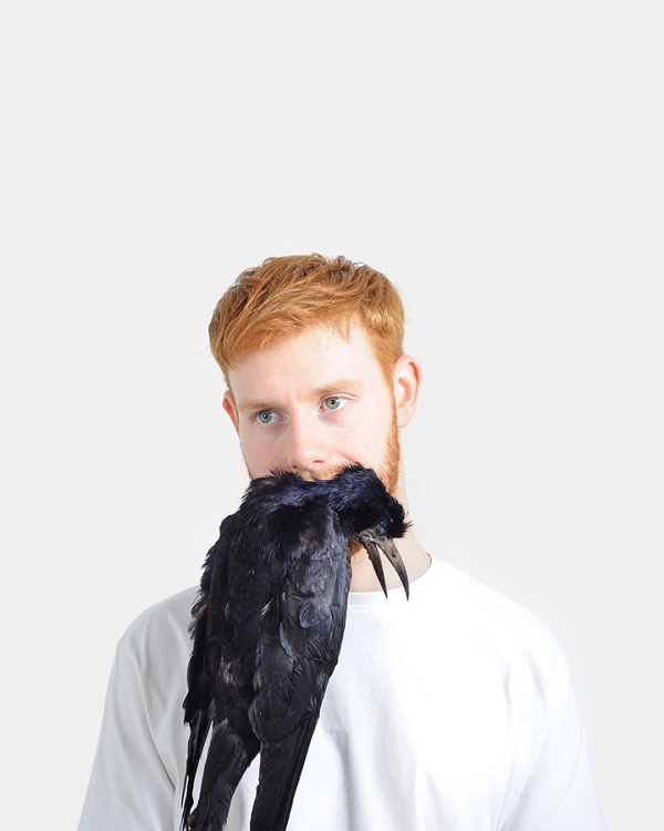 bizarre portraits of man holding dead animals in his mouth