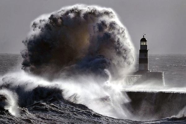 wave crashing over lighthouse