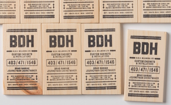 Carpenter rubber stamps business card information onto wooden blocks via for print only colourmoves