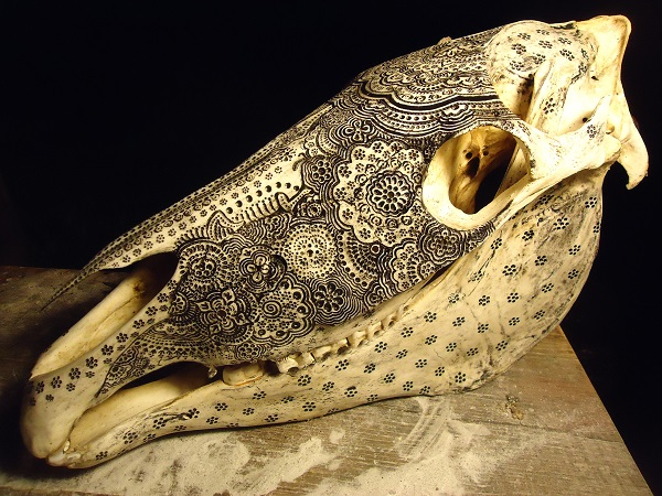 artist carves intricately detailed patterns on animal